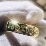 Gullring med flere små diamanter som holdes av hvit hanske