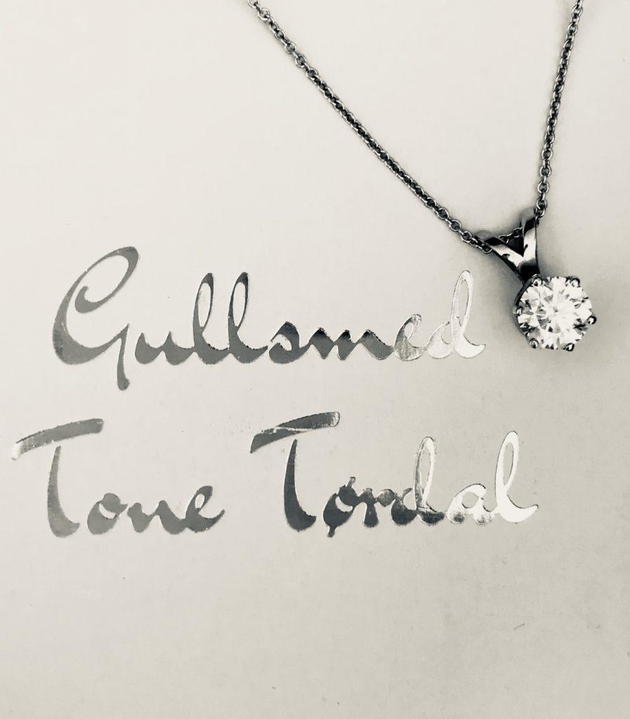 Diamantsmykke i anheng ved siden av skrift med Gullsmed Tone Tørdal