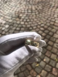 Gullring med flere diamanter, holdt i hvit hanske