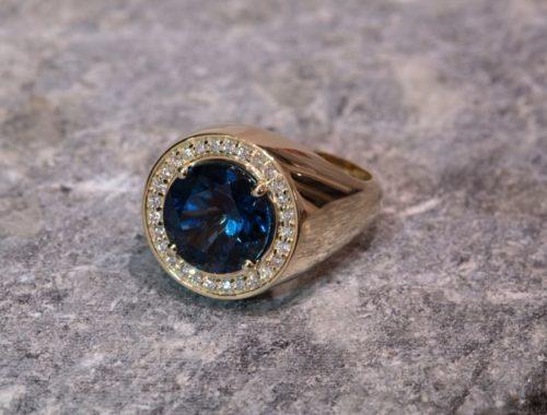 Ring med blå stein og små diamanter rundt